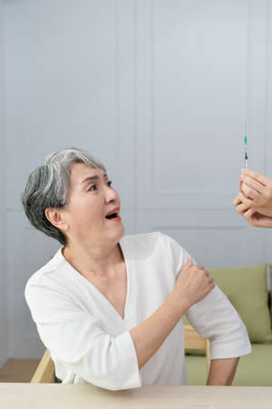 refusing vaccine injection into senior woman shoulder, She showed a scared expression.