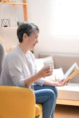 Elderly retired at home, enjoy life, reading book. Stock Photo