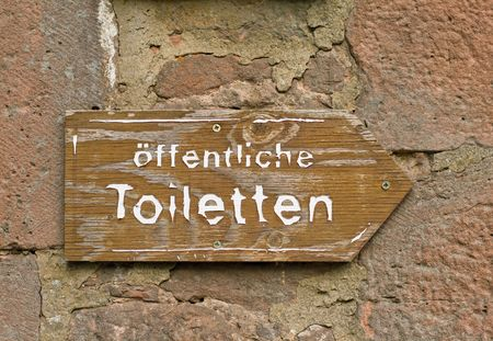 A wooden sign of public toilets on a stone wall photo