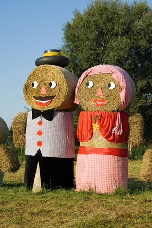 Two figures made out of straw bales, man, woman, father, mother, on a meadow photo
