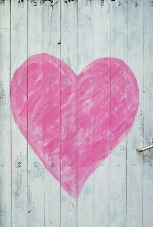 A white wooden door with a pink heart