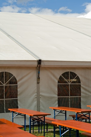 A white party or event tent with beer tables and benches