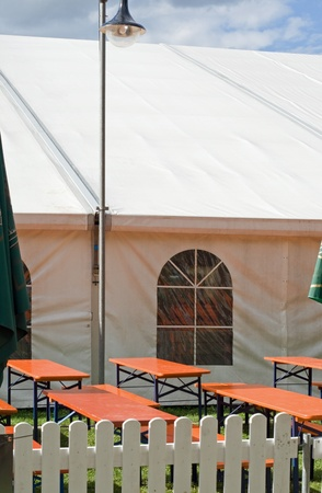 A white party or event tent with beer tables and benches and lantern photo