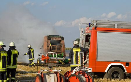 baler: Firefighters extinguish a burning round baler on a field
