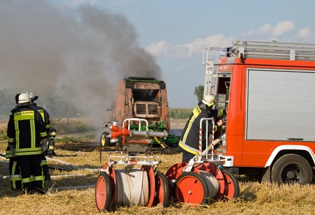 Firefighters extinguish a burning round baler on a field
