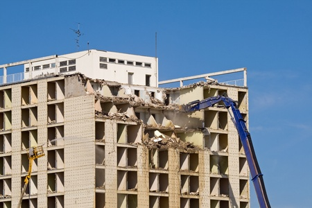 stone cutter: Machine taking down a large residential building
