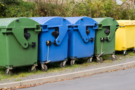 Two blue paper containers, yellow recycling container and two containers for organic waste