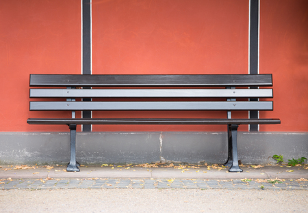 late summer: An empty bench on a house wall in late summer Stock Photo
