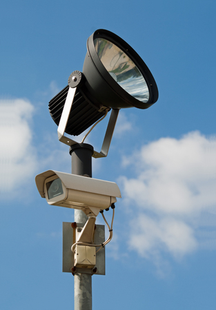 big brother spy: C�mara de vigilancia con reflector, cielo nublado azul
