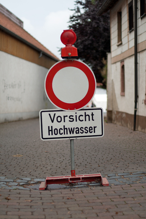 climatology: German sign that means passage forbidden with additional sign that says caution flood