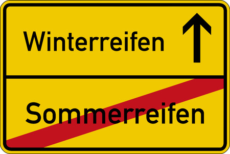 The German words for winter tires and summer tires (Winterreifen and Sommerreifen) on a road sign Standard-Bild