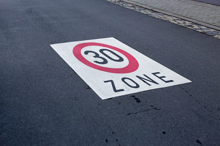 kph: Speed limit 30 painted on asphalt cobblestones