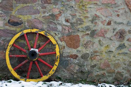 carreta madera: Rueda de carro de madera en una pared de piedra en invierno