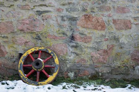 carreta madera: Dos ruedas de carro de madera vieja en un muro de piedra en invierno