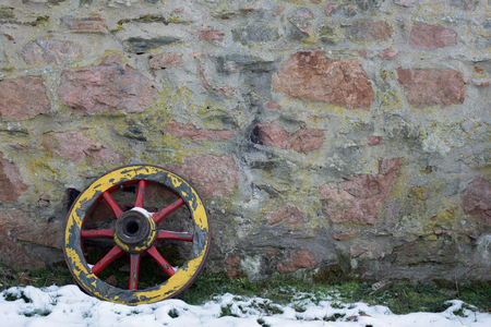 two wheel: Two old wooden wagon wheel on a stone wall in winter