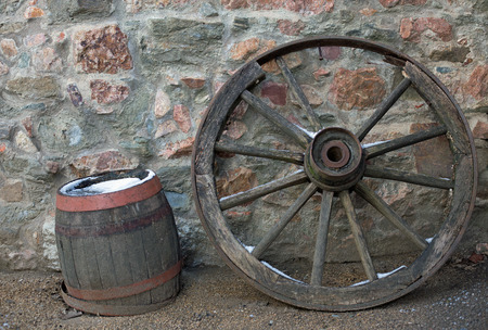 wheel barrel: Old wooden wagon wheel and barrel on a stone wall in winter