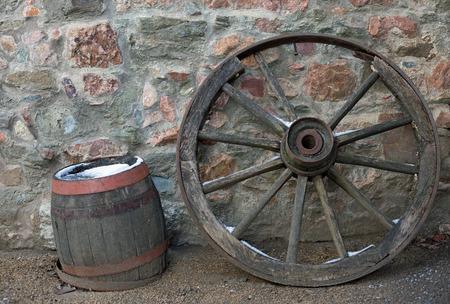 carreta madera: Rueda de carro de madera y el ca��n en una pared de piedra en invierno