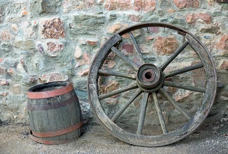 carreta madera: Rueda de carro de madera y el ca��n en una pared de piedra Foto de archivo