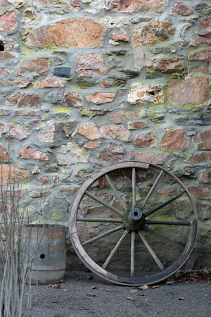 wheel barrel: Old wooden wagon wheel and barrel on a stone wall