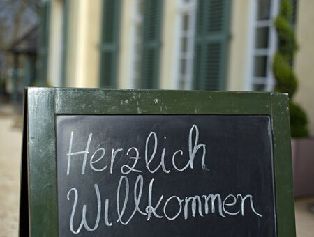 warmly: Blackboard that says handwritten warmly welcome german Herzlich Willkommen