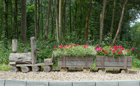 wood railways: Wooden train with flowers on gravel, in the background trees