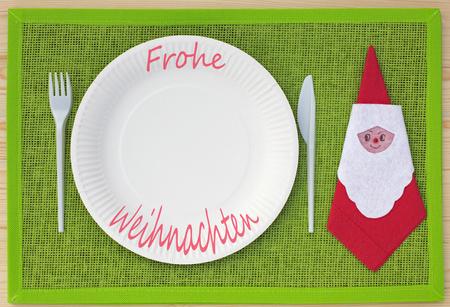 servilleta de papel: Cuchillo, tenedor, servilleta y placas de cartón en lugar de verde set y las palabras alemanas para Feliz Navidad (Frohe Weihnachten)