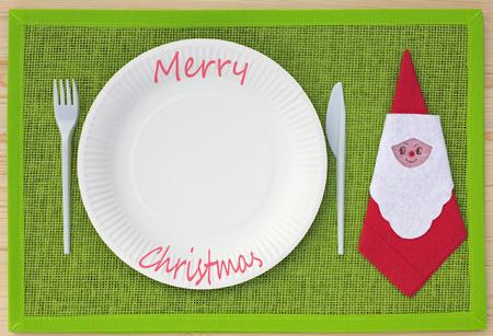 servilleta de papel: Cuchillo, tenedor, servilleta y placas de cartón en lugar conjunto verde y las palabras Feliz Navidad