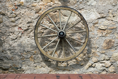 carreta madera: Old wooden wagon wheel on a stone wall Foto de archivo
