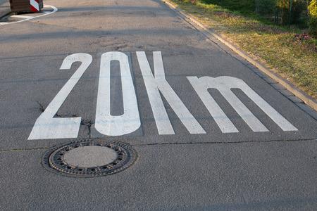 kph: Speed limit 20 painted on asphalt