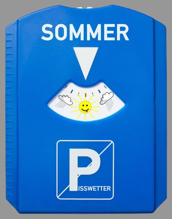 A german parking disc with the german words for summer and bad weather isolated on grey