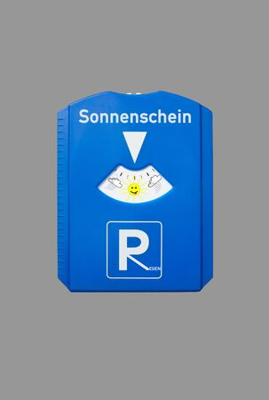 A german parking disc with the german words for sunshine and rain isolated on grey