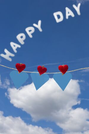 Three hearts with clothes pegs and three hearts of paper on a cord and text Happy Day