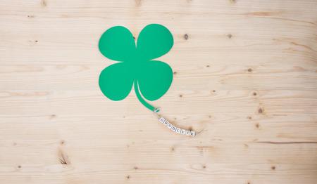 cloverleaf: The words Good Luck and a cloverleaf on a cord on wood