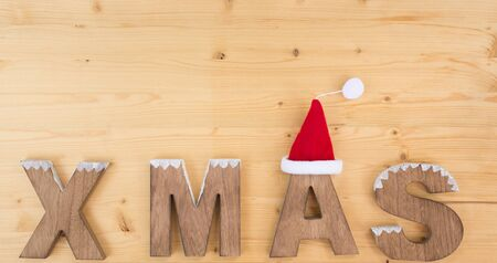 The word X MAS made on wood on wood and santa claus hat