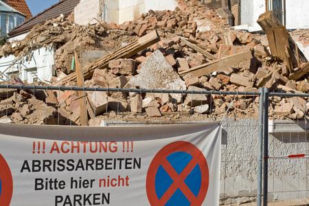 Demolition. Note on a fence: Achtung. Abrissarbeiten. Bitte hier nicht parken (Demolition work. Please do not park here). Behind a demolished house. Stock Photo