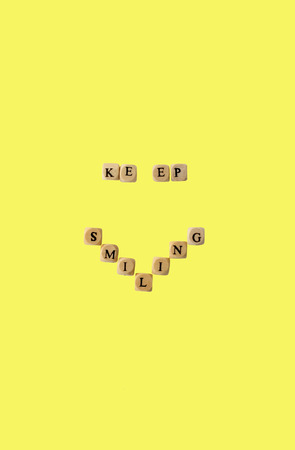 The words keep smiling, isolated on yellow