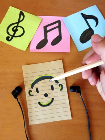 Writing Musical Notes and Listening to song  Stock Photo