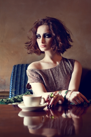 Beautiful brunette woman sitting alone in a restaurant with a cup of coffee photo