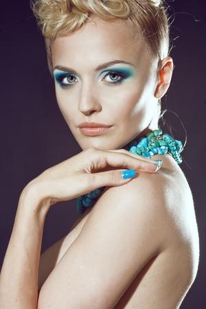 유행: 청록색의 메이크업과 액세서리와 함께 아름 다운 섹시 한 젊은 여자
