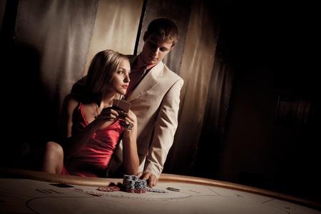cartas de poker: Hombre joven y mujer jugando al póquer en el casino