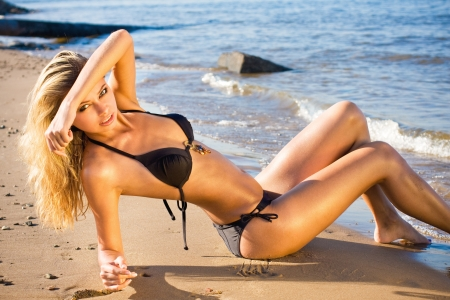 tanned body: Young beautiful sexy blonde bikini model, laying on sea beach