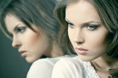 Face of a beautiful girl with her reflection in the mirror Stock Photo - 16230014