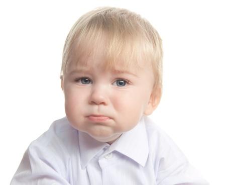 Sad little boy isolated on white photo