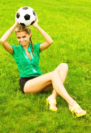 Beautiful girl with a classical soccer ball sitting on the grass photo