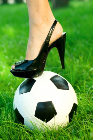 Female's foot in black shoe with high heel standing on a soccer ball in green grass photo