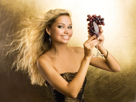 Beautiful young sexy woman with a grape photo