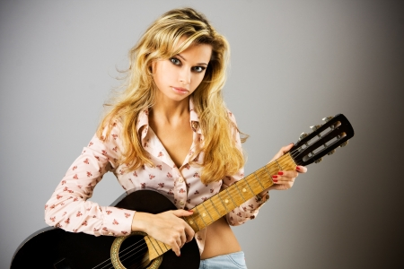 Studio portrait of a beautiful sexy young woman with black guitar photo
