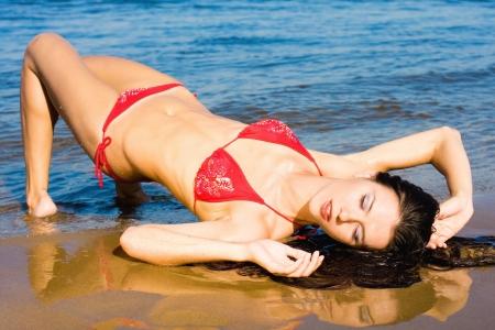 Beautiful young sexy woman in red bikini at the beach photo