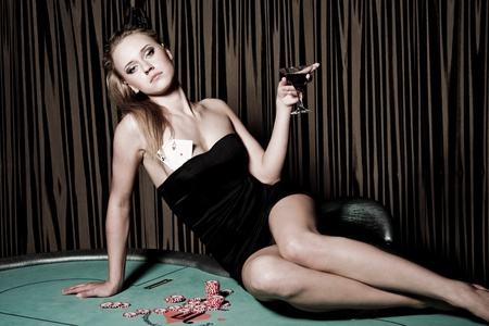 Sexy young girl with glass of wine in casino Stock Photo