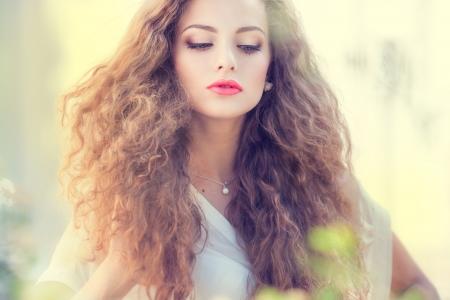 야외에서 화려한 곱슬 공정을 가진 아름 다운 젊은 여자